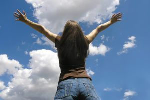 young woman holding her arms up to the open sky
